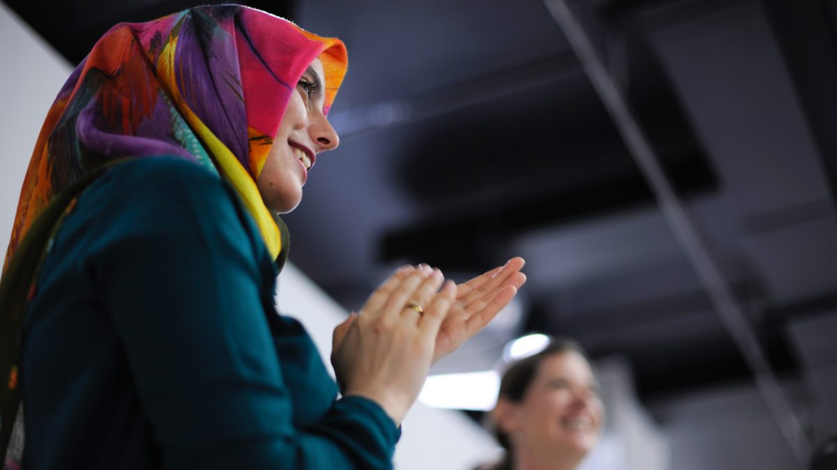 Clapping woman in a headscarf. Photo by rawpixel.com on Unsplash