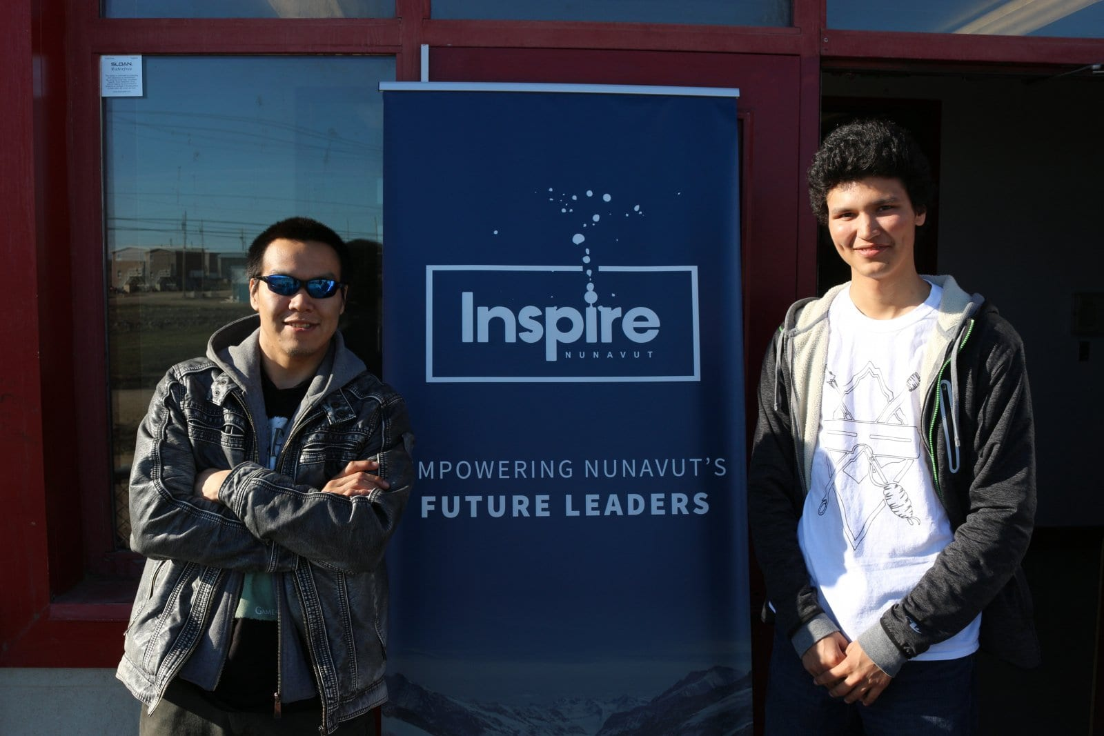 Two young men stand beside Inspire Nunavut sign